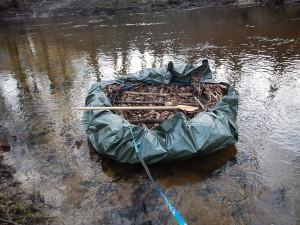 Survival Korbboot aus Ästen, Laub, Schnur und Plane